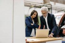 Uomo d'affari e donna d'affari nell'impresa high-tech, avendo un incontro, utilizzando il computer portatile — Foto stock