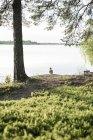 Bambina solitaria in piedi al lago in campagna — Foto stock