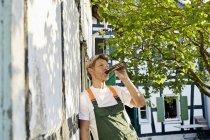 Uomo maturo in piedi in giardino indossando grembiule, bere birra — Foto stock