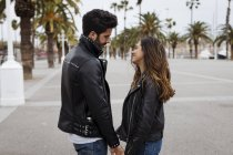 Smiling romantic young couple on promenade with palms — Stock Photo