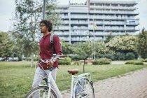Jeune homme avec sac à dos poussant vélo dans le parc — Photo de stock