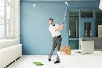 Бизнесмен играет в гольф в современном офисе — стоковое фото