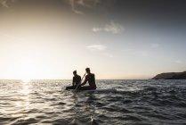 Pareja en remo en el paddleboard al atardecer en el mar - foto de stock