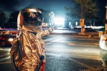 Spaceman on street in city at night pointing at shining projection screen — Stock Photo