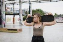 Joven mujer fresca que lleva monopatín en la ciudad - foto de stock