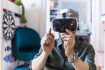 Portrait of mature man at home using Virtual Reality Glasses — Stock Photo