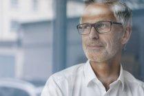 Manager di successo guardando fuori dalla finestra, pensando, ritratto — Foto stock