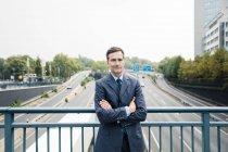 Портрет уверенного бизнесмена, стоящего на мосту — стоковое фото