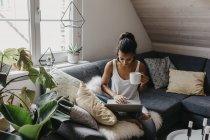 Молодая женщина сидит на диване с чашкой кофе с помощью ноутбука — стоковое фото