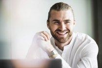 Retrato de jovem empresário sorridente no cargo — Fotografia de Stock