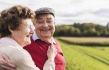 Счастливая пожилая пара, обнимающаяся в сельской местности — стоковое фото