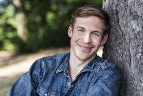 Портрет улыбающегося мужчины, сидящего летом на открытом воздухе — стоковое фото