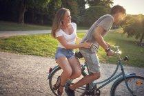 Молода пара їзда на велосипеді в парку, жінка, сидячи на стійці — стокове фото