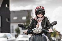 Actif dame âgée équitation scooter moteur en ville — Photo de stock