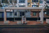 Spaceman sitting on bench at bus stop at night with drink — Stock Photo