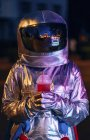 Spaceman in city at night with takeaway drink — Stock Photo