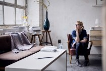 Пенсионерка сидит на кресле в мансарде и смотрит в окно — стоковое фото