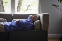 Зрелый мужчина лежит дома на диване — стоковое фото
