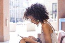 Mujer joven con el pelo rizado sentado y usando tableta digital en la ciudad - foto de stock