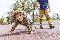 Spagna, Barcellona, giovane ragazzo che striscia accanto al padre sul lungomare — Foto stock