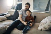 Счастливый отец и сын сидят вместе на диване и играют в компьютерные игры. — стоковое фото