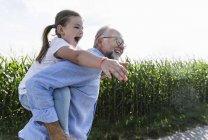 Abuelo llevando a su nieta a cuestas - foto de stock