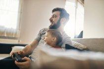 Отец и сын сидят вместе на диване и играют в компьютерные игры. — стоковое фото