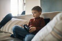 Портрет мальчика, сидящего на диване и играющего в компьютерные игры — стоковое фото