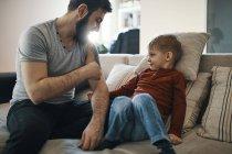 Отец сидит на диване с маленьким сыном, показывая свою татуировку. — стоковое фото