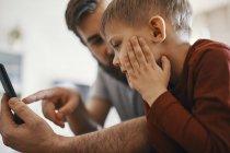 Padre e figlioletto con smartphone — Foto stock
