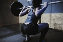 Woman lifting barbell in gym — Stock Photo