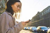 Rússia, St Petersburg, mulher nova que usa o smartphone na cidade — Fotografia de Stock