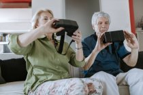 Senior couple at home sitting on couch holding VR glasses — Stock Photo