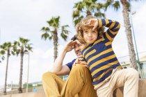 España, Barcelona, padre e hijo sentados en la playa mirando a la distancia - foto de stock