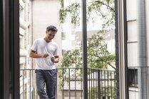 Homme souriant en pyjama avec tasse de café debout sur le balcon — Photo de stock