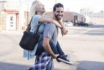 Jovem feliz carregando namorada piggyback — Fotografia de Stock