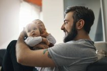 Happy father with baby girl and little son together at home — Stock Photo