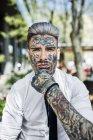 Молодой бизнесмен с татуированным лицом, смотрит в камеру — стоковое фото