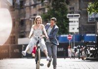 Felice coppia spensierata con bicicletta in città — Foto stock