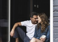 Ласковая пара в ночной сорочке сидит дома у французского окна — стоковое фото