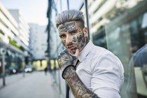 Молодой бизнесмен с татуированным лицом гуляет по городу, портрет — стоковое фото
