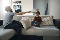 Father and little son playing together on the couch in the living room — Stock Photo