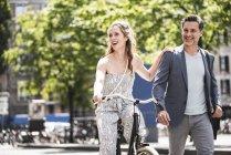 Coppia felice con bicicletta in città — Foto stock