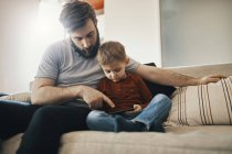 Father and little son sitting together on the couch looking at smartphone — Stock Photo
