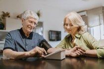 Старшая пара измеряет давление — стоковое фото