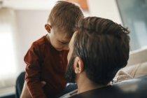Отец и сын играют вместе на диване — стоковое фото