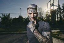 Retrato de jovem tatuado na quadra de basquete — Fotografia de Stock