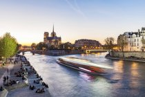France, Paris, Tourist boat on Seine river with Notre Dame cathedral in background — Stock Photo