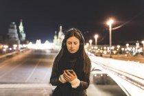 Росія, Москва, прекрасна жінка слухає музику в місті вночі — стокове фото