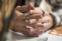 Plan rapproché des mains de l'artiste se reposant sur la table — Photo de stock